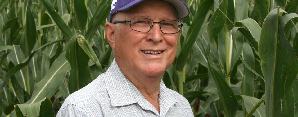 Outstanding Alumni Stahlman standing in a corn field