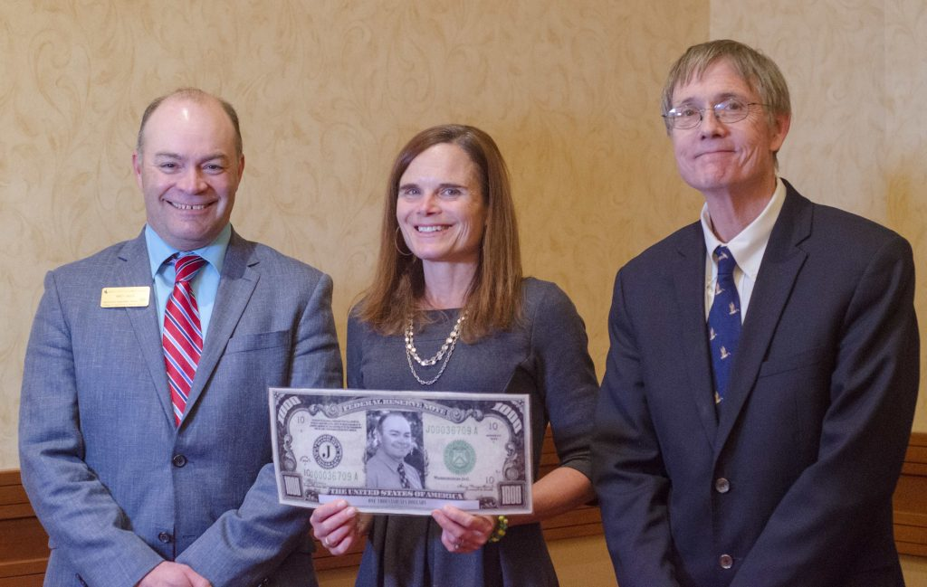 Award winner holding pretend money and flanked by two men.