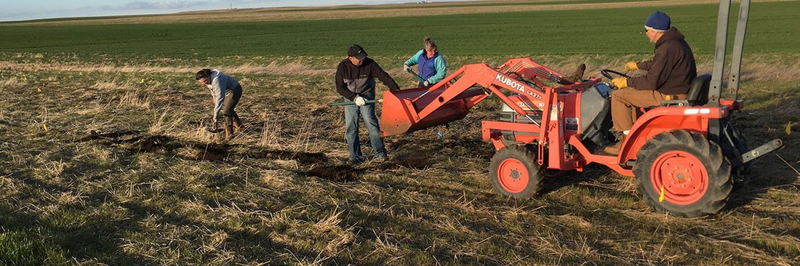 Workers are in a field are unloading material from a tractor loader.