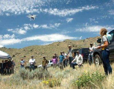 Woman flying a drone while group of people observers.