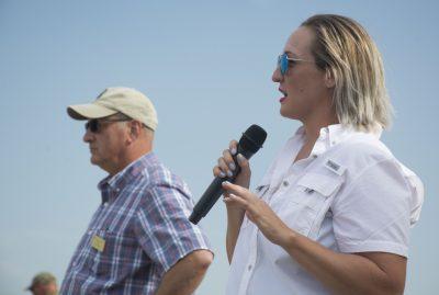 Woman in field speaks into microphone.