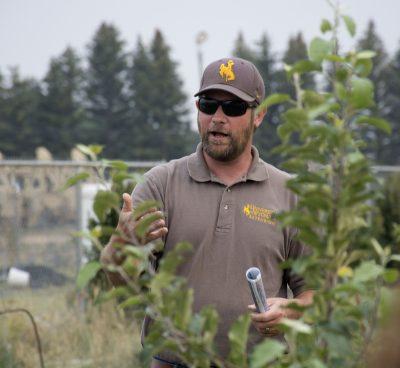 Man standing near tree wearing hat