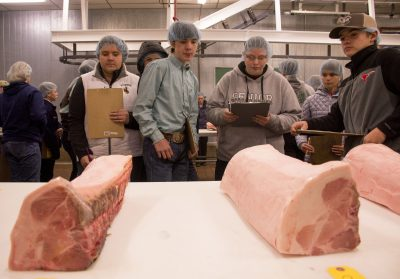 Youths stand in freezer in front of meat