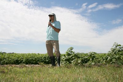 Man in hat standing in a field with microphone