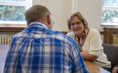 Dean Barbara Rasco visits with person.