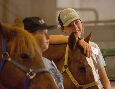 4-H'er leans her arm on horse