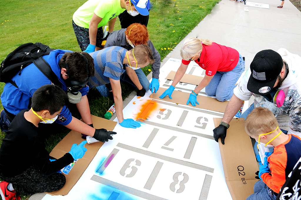 A group gathers around the hopscotch stencil.