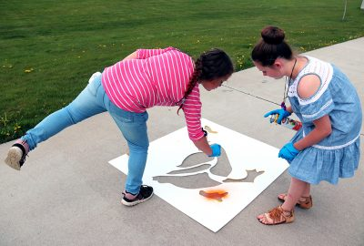 Two girls paint the duck stencil.