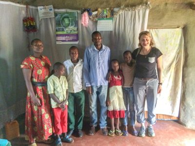 3 adults and 4 children standing in a row in a house in Africa.