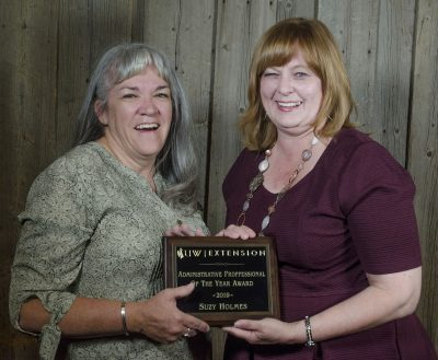 Two women hold a plaque