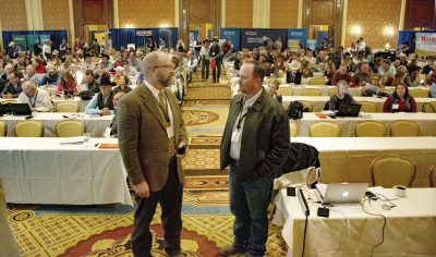 Photograph of two men standing in front of conference attendees