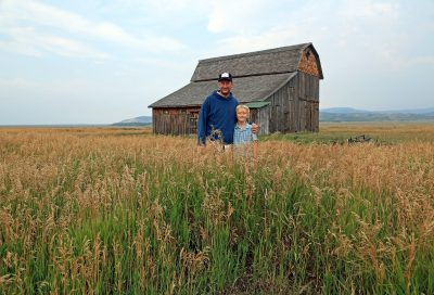 Father and son in field in front of old brown barn.
