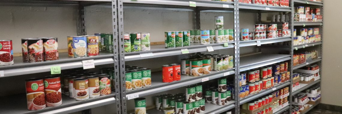 Metal shelving with organized cans of food.
