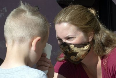 Woman takes forehead temperature of young boy