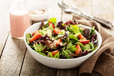 dressed salad in white bowl