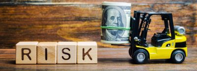 Wood blocks that spell RISK next to toy forklift carrying a roll of $100 bills.