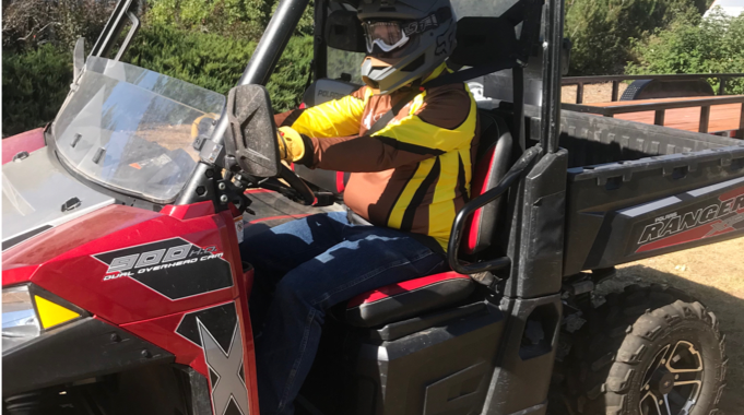 Red 4-wheel ATV with black canopy. Driver in blue jeans, yellow and brown shirt, black helmet.