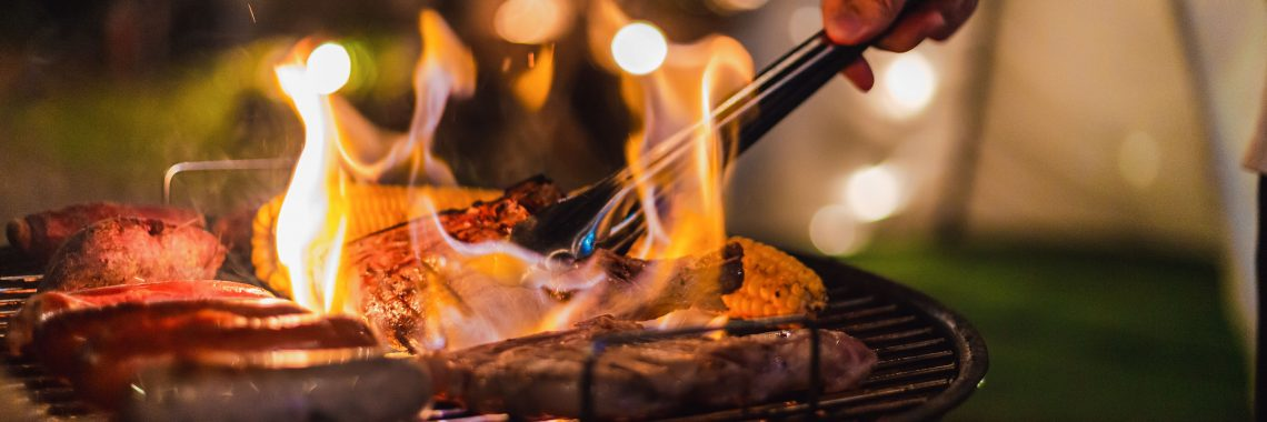 various meats on grill with flames and someone reaching in with tongs to flip one of the pieces of meat