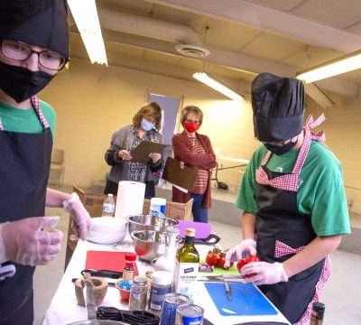 Photograph of 4-H'ers in masks preparing food