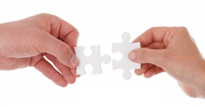 Hands putting two puzzle pieces together