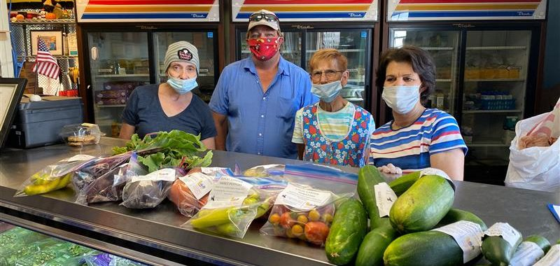 Four individuals standing behind produce fridge