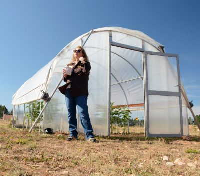 Lady standing near a hoop house