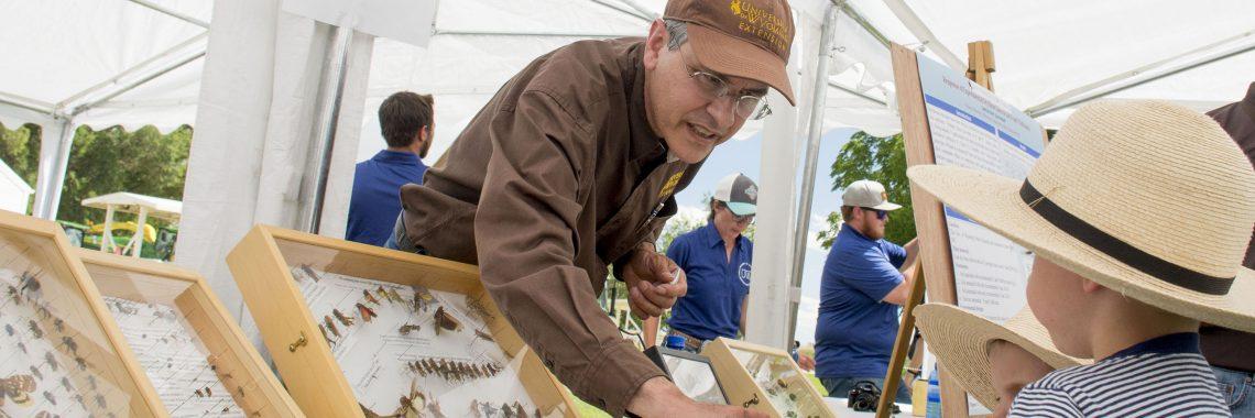 Man teaching child about entomology