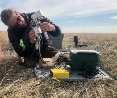 Man with mechanical sensor kneeling in field