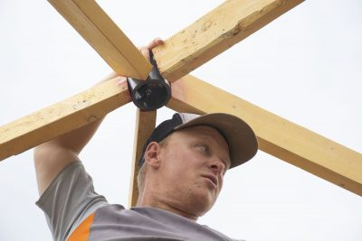 Man with hands on wooden supports