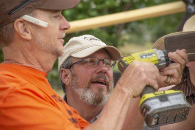 Two people secure plastic sheathing