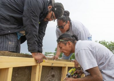 three people attaching wood pieces together