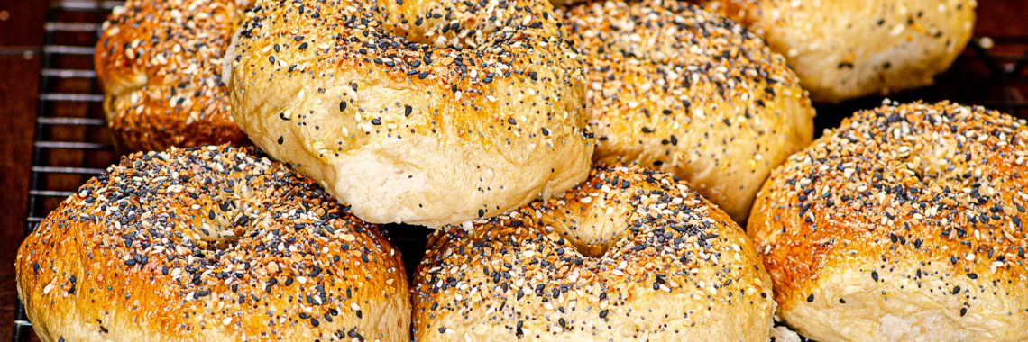 Bagels topped with sesame seeds, poppy seeds, minced garlic, and minced onion.