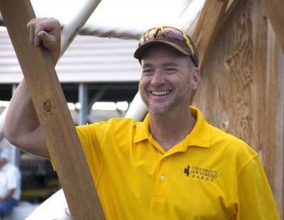 Man standing in UW Extension shirt, hat